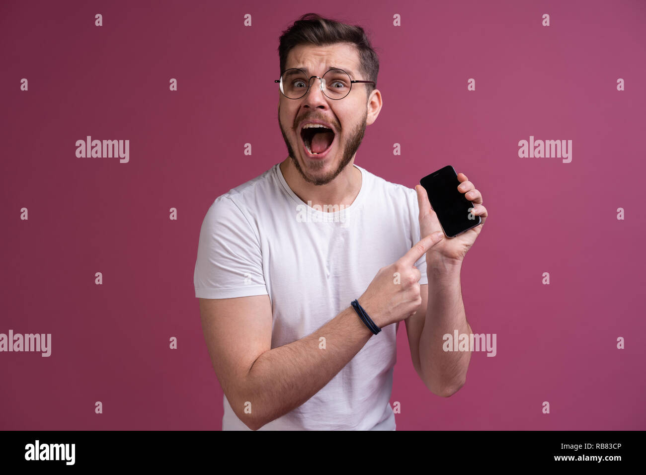 You will have problems man! Portrait of angry confused aggressive in bad mood guy shouting threatening in the loud-speaker of his smartphone, isolated on pink background. - Stock Image
