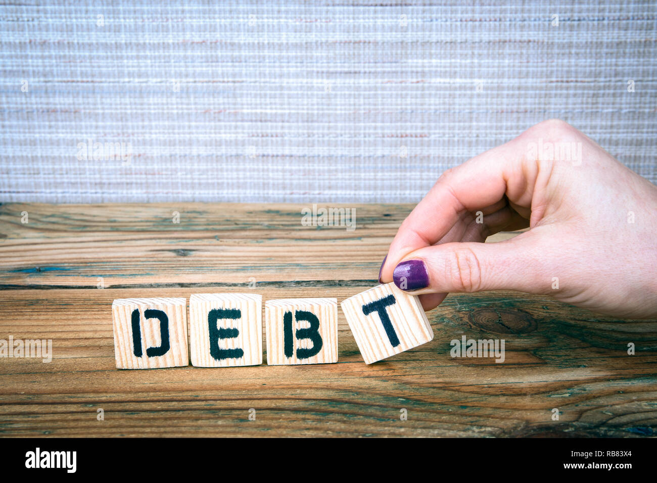 debt. Wooden letters on the office desk - Stock Image