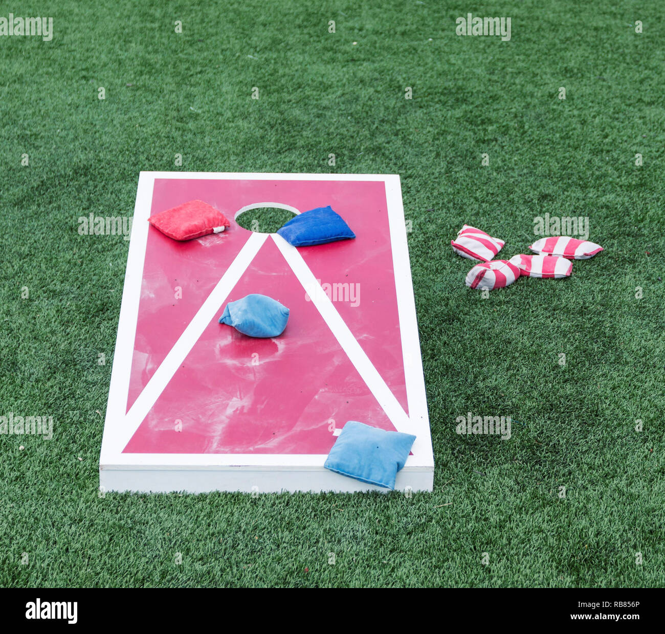 Playing the popular game corn hole on a red and white wood board with blue and red striped bean bags on turf. - Stock Image
