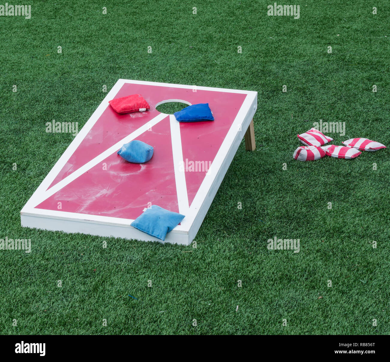 A cornhole board is set up with colorful beanbags resting on it after the competitors have thrown them. - Stock Image