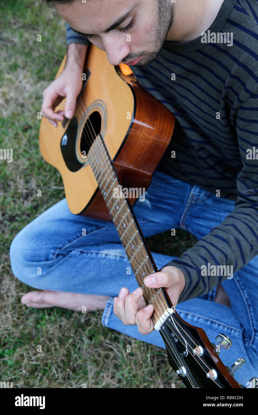 Young man playing a guitar in a garden. France. - Stock Image