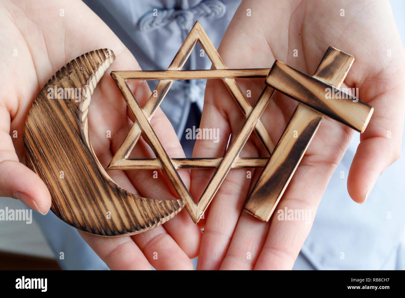 Symboles interreligieux. Christianity, Islam, Judaism 3 monotheistic religions. Jewish Star, Cross and Crescent : Interreligious symbols in hands. Stock Photo