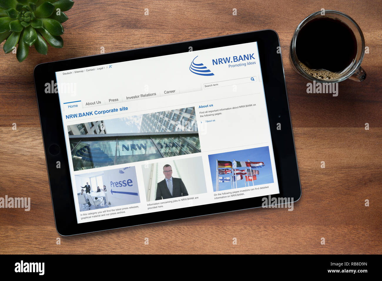 The website of NRW Bank is seen on an iPad tablet, on a wooden table along with an espresso coffee and a house plant (Editorial use only). - Stock Image