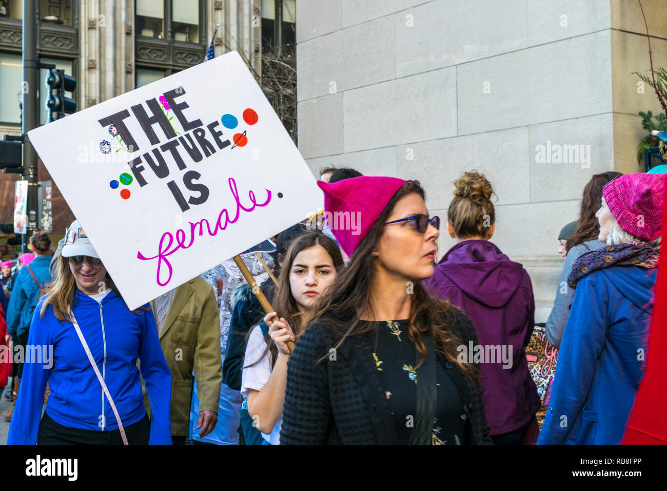 """Chicago, IL, United States - January 21, 2017: Girl holds a picket sign that reads """"The Future Is Female"""" during Women's March in Chicago on January 2 Stock Photo"""