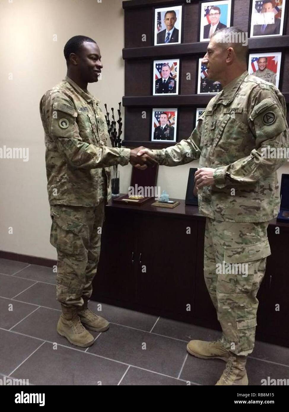 Spc. Chaztein M. Sheats, secetary general staff executive administrative assistant, 1st Sustainment Command (Theater), received a commander's coin for his outstanding service and dedication to duty from Maj. Gen. William Hickman, deputy commanding general, operational command post, United States Army Central, Dec. 17, at Camp Arifjan, Kuwait.     Sheats went above and beyond working outside his assigned duties and assisted the ARCENT and 29th Infantry Division G1 Personnel sections for more than 60 days. - Stock Image
