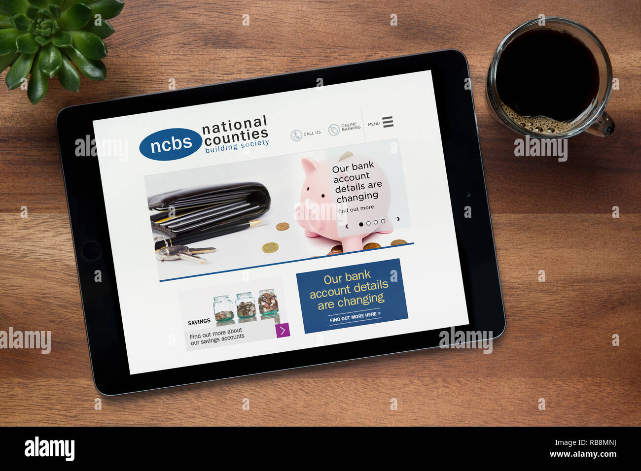 The website of National Counties Building Society is seen on an iPad tablet resting on a wooden table (Editorial use only). - Stock Image