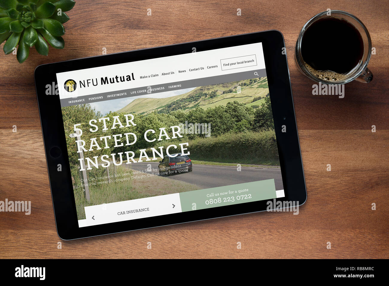 The website of NFU Mutual is seen on an iPad tablet, on a wooden table along with an espresso coffee and a house plant (Editorial use only). - Stock Image