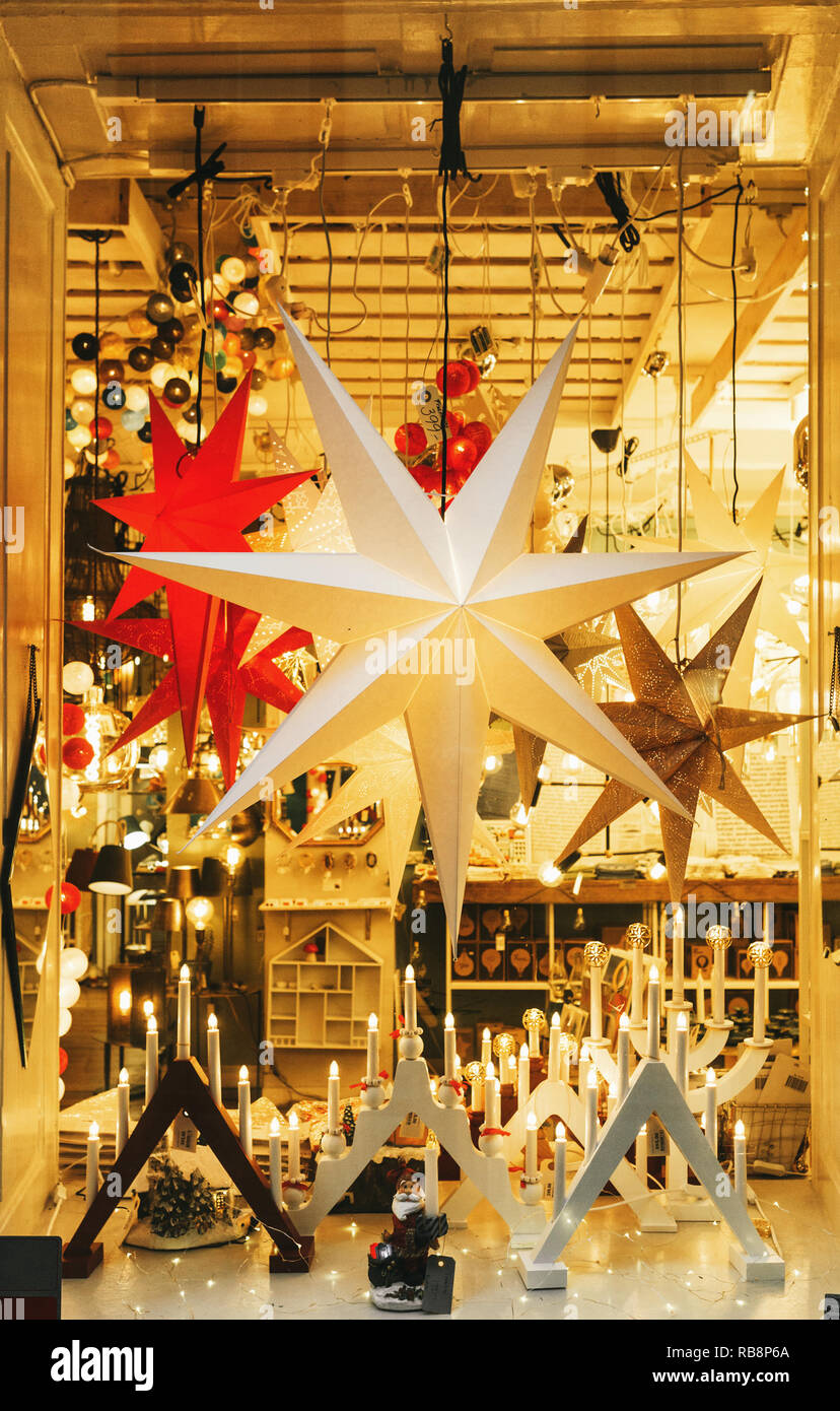 Christmas stars and candles decorations in window. Festive decor in the shop window .Stockholm, Sweden Stock Photo
