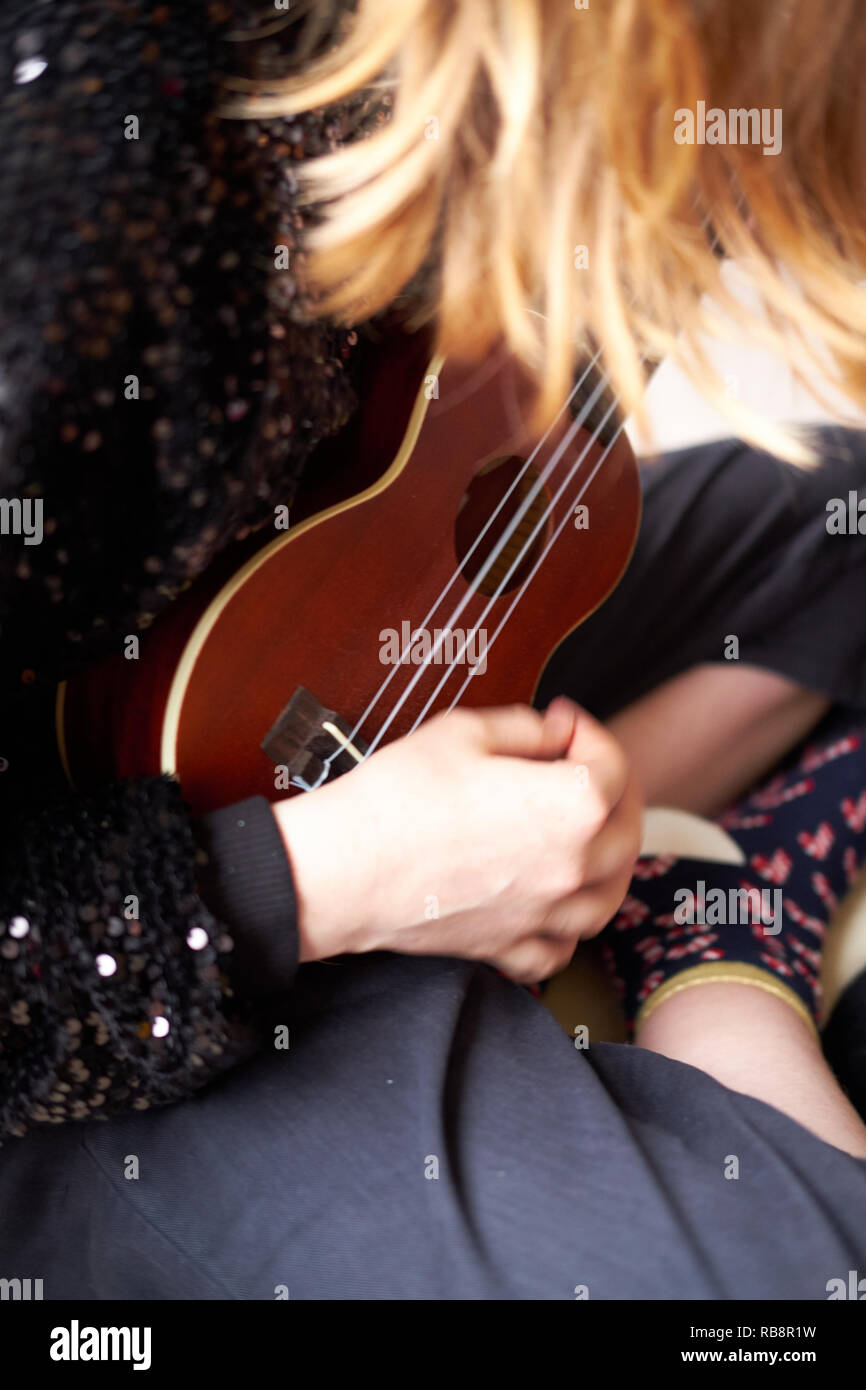 Close up of a girl playing a ukulele stringed instrument - Stock Image