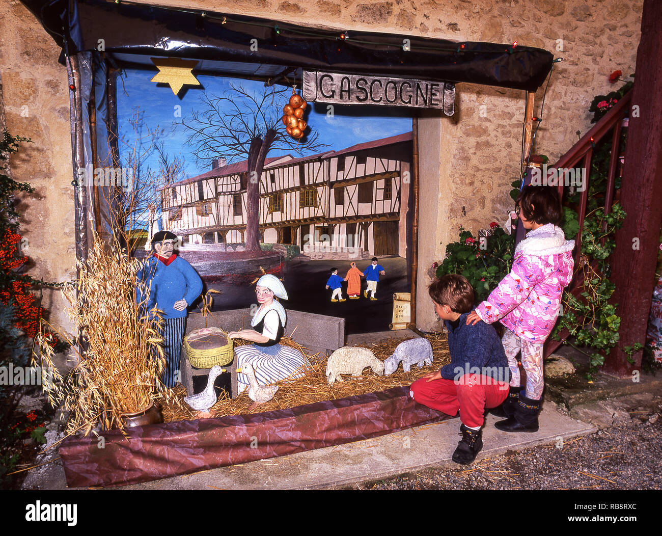 Children looking at a Christmas tableau they helped to build in their village main square. - Stock Image