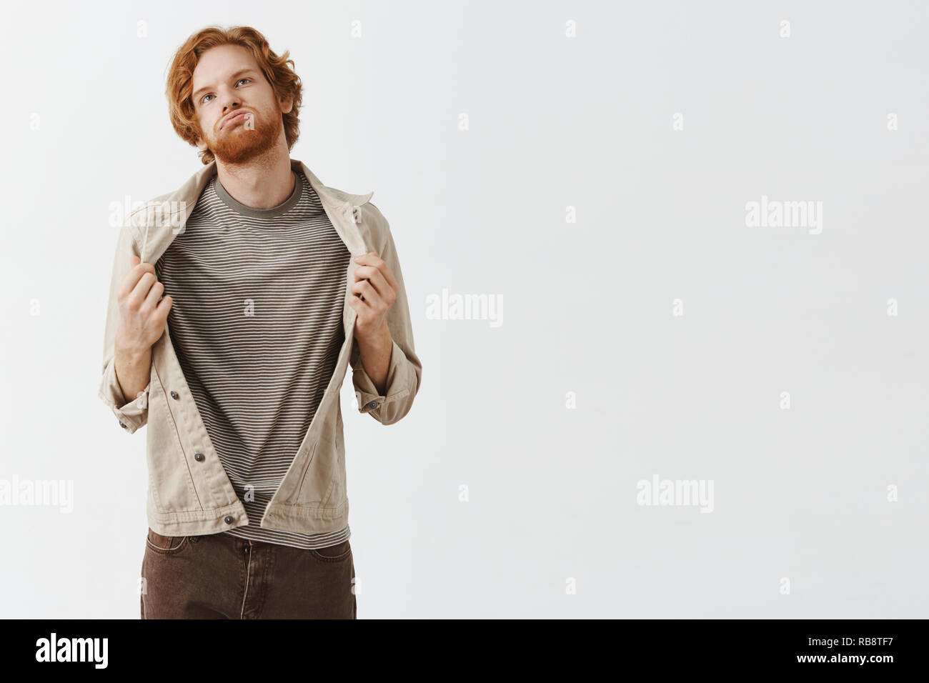 Redhead guy picked wrong clothes feeling boiling hot in warm jacket breathing out waving with cloth, looking up at sun feeling discomfort standing displeased and bothered over gray background - Stock Image