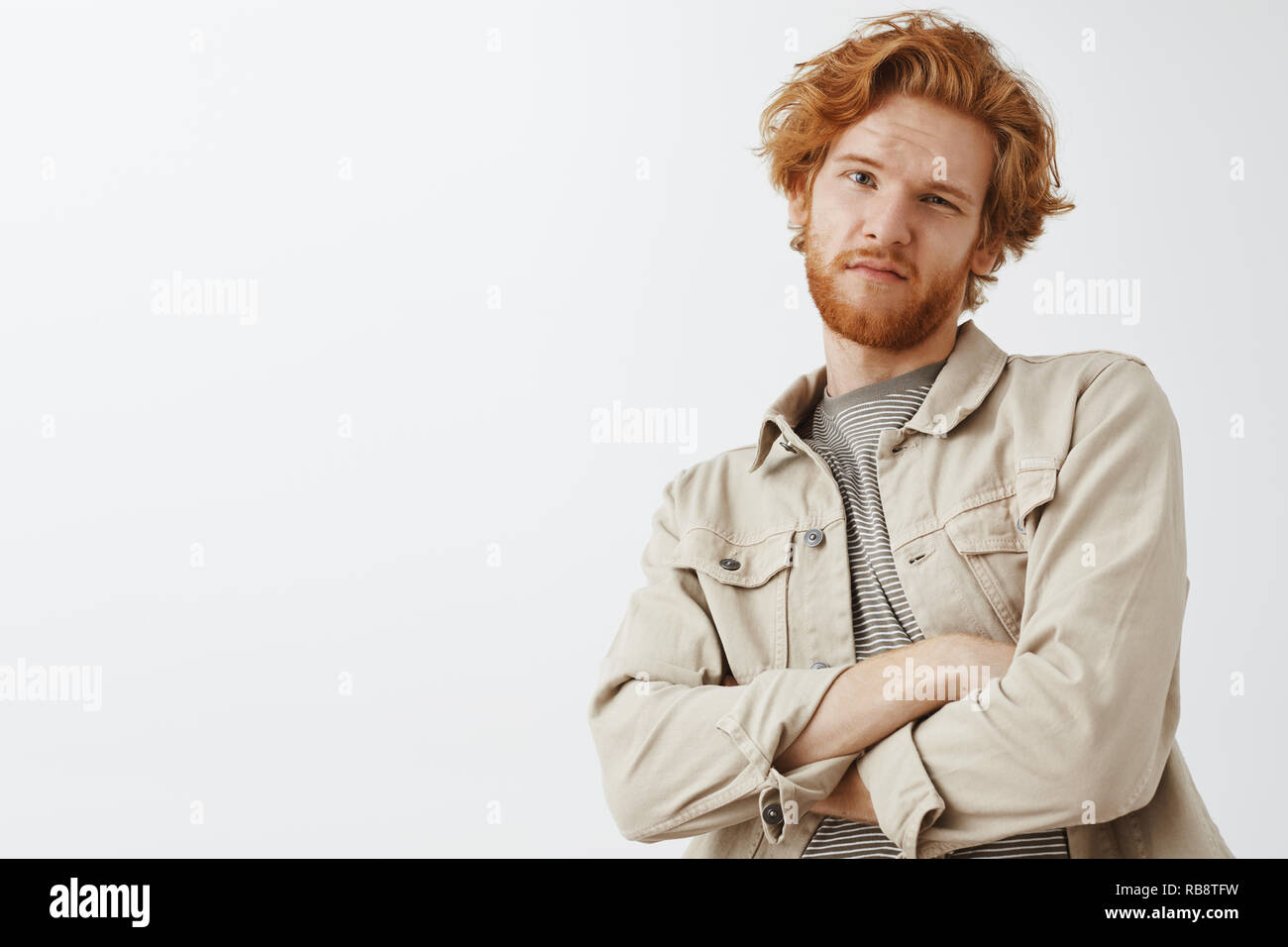 Oh not impressive. Portrait of cool snobbish redhead guy with wavy hair and beard tilting backwards with hands crossed on chest and doubtful unimpressed expression being disappointed - Stock Image