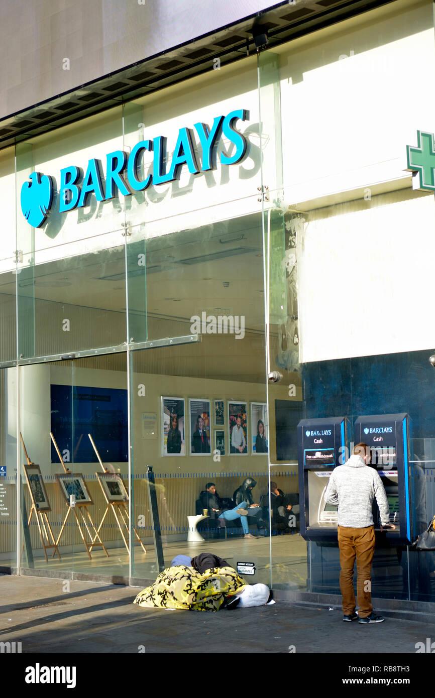 Homeless man sleeping outside Barclays Bank, Piccadilly Circus, London, England, UK. - Stock Image