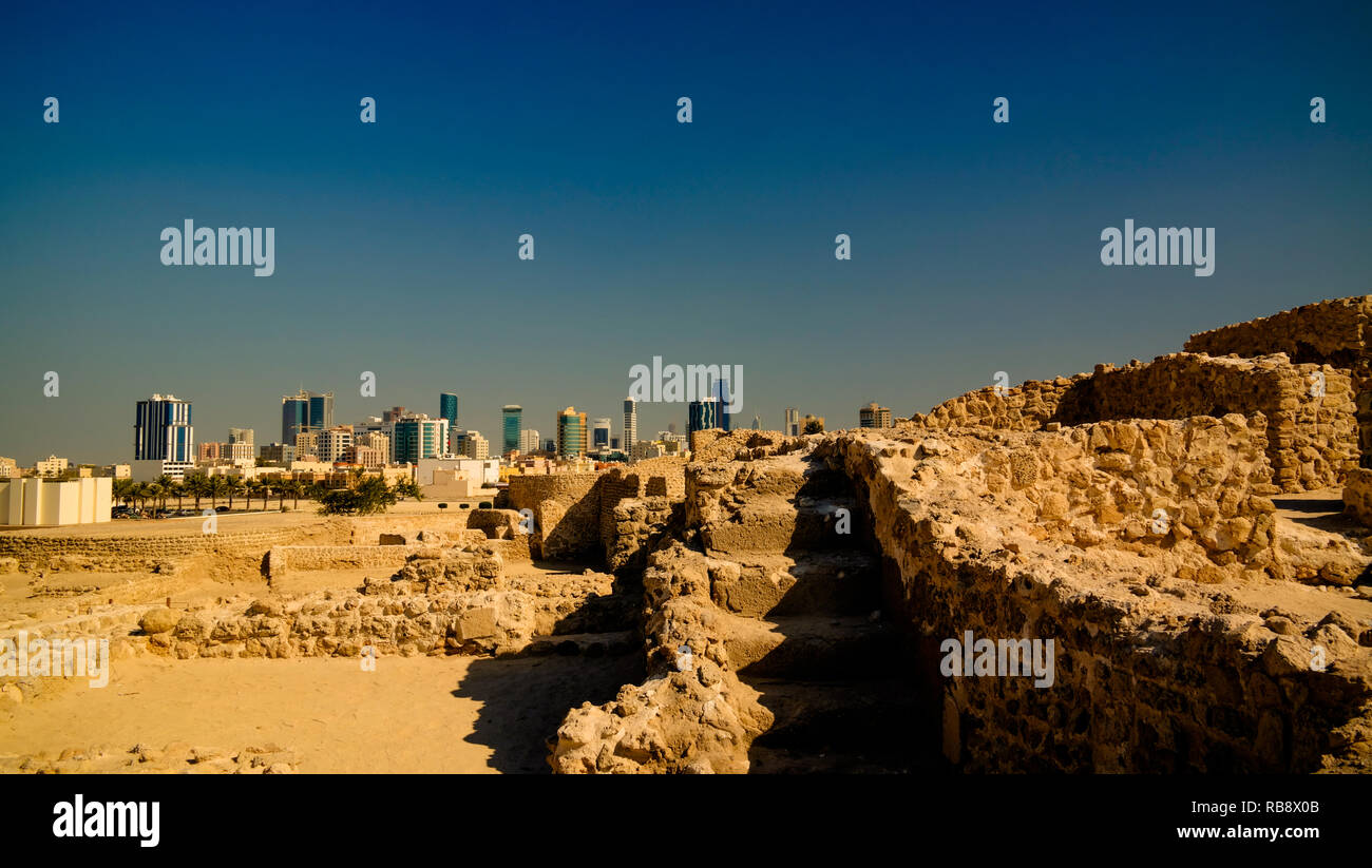 Ruins of Qalat fort and Manama in Bahrain - Stock Image