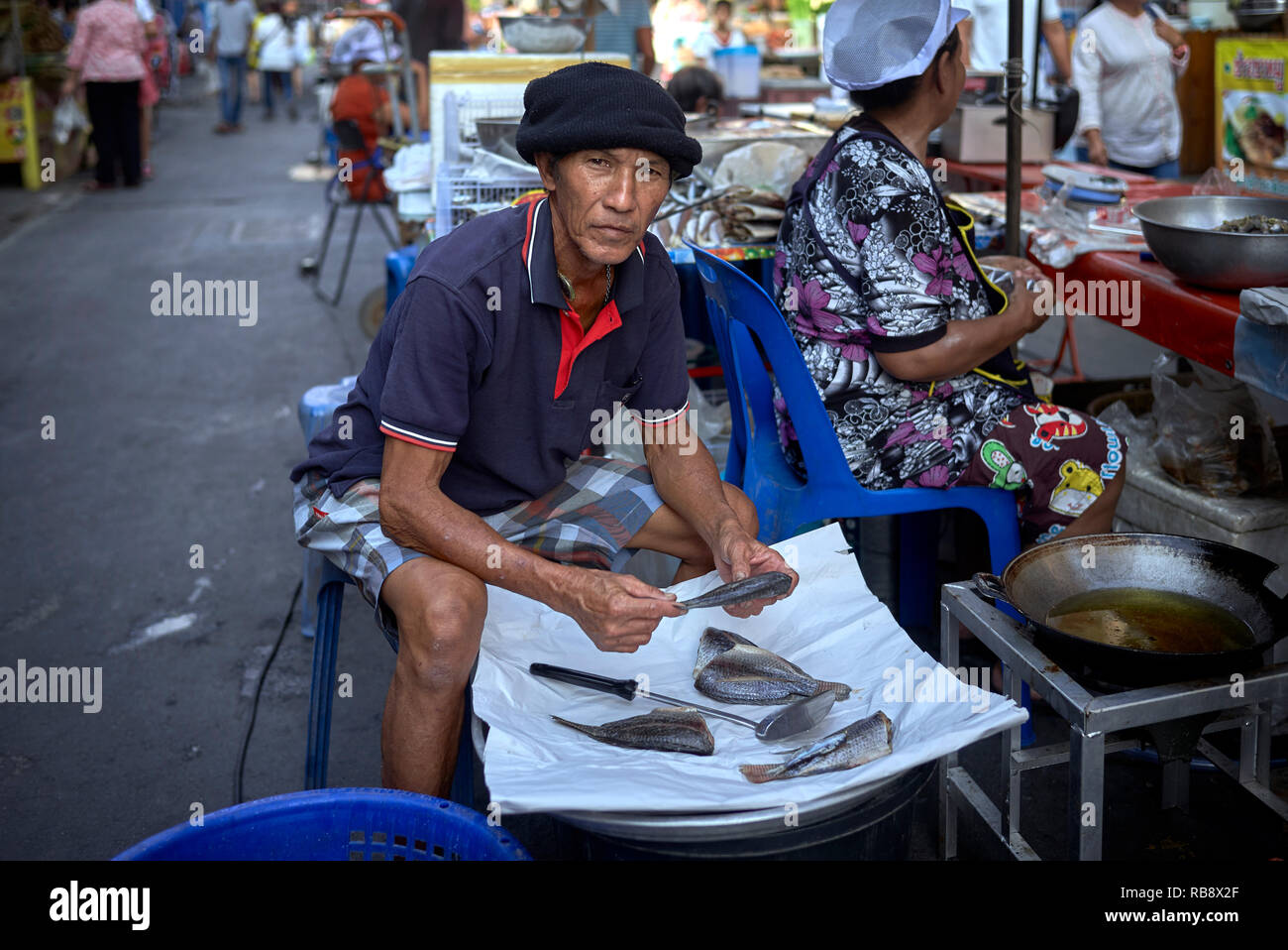 Thailand street food market vendor preparing fish for sale. Southeast Asia - Stock Image