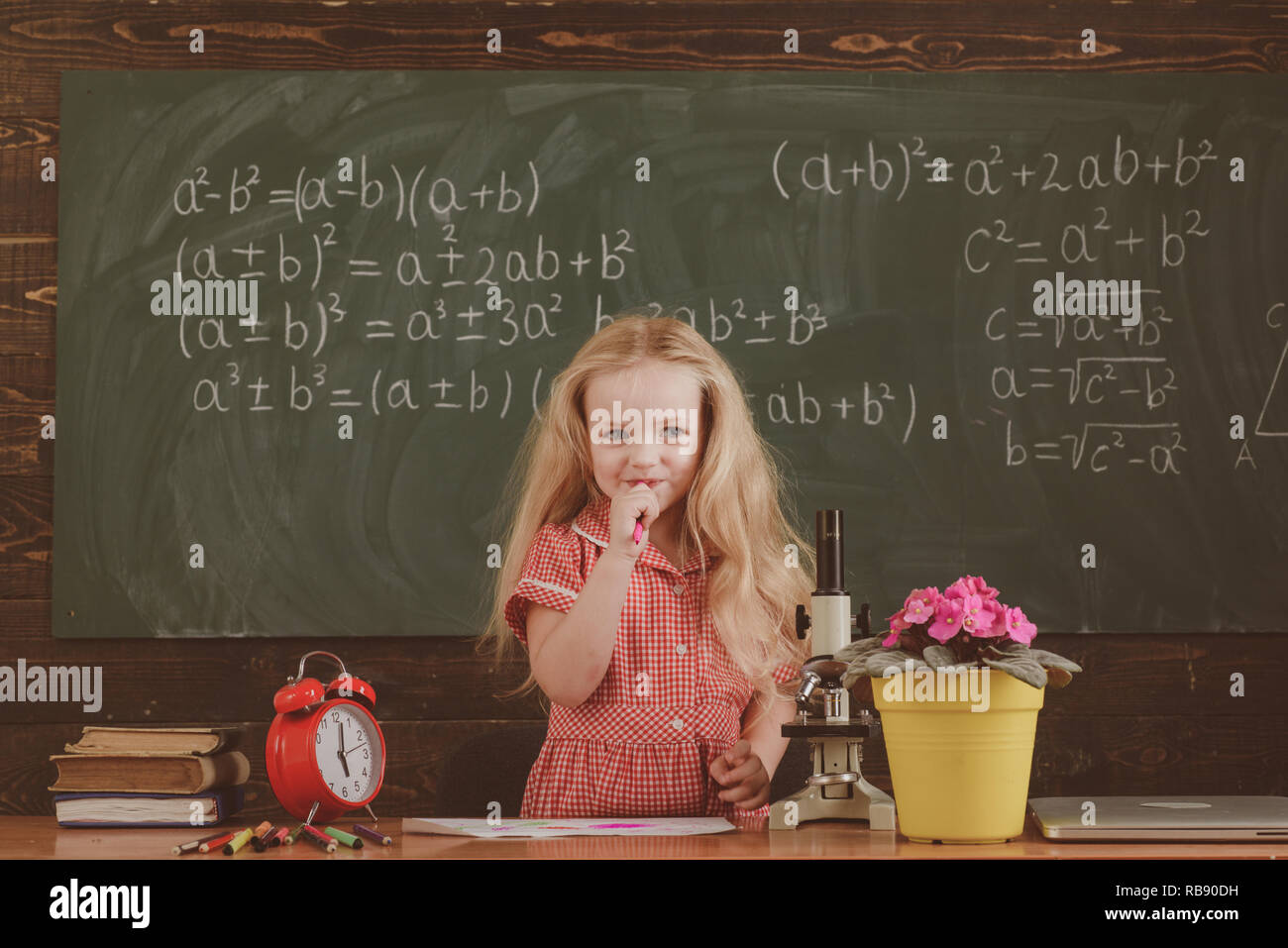 Little girl think of mathematical problem in classroom. Schoolchild solve problem in school - Stock Image