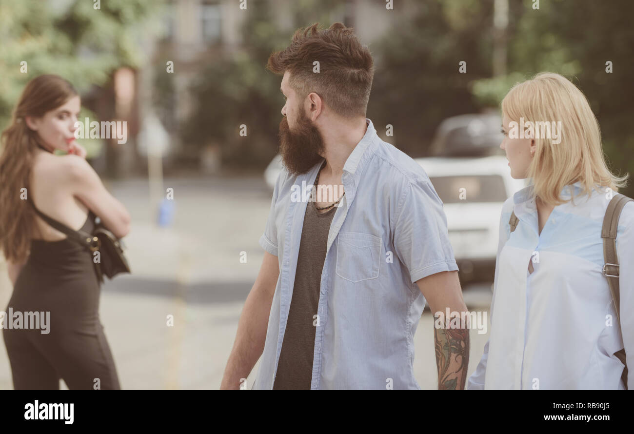 Relationship problem. Man cheating his wife or girlfriend. Bearded man looking at other girl. Hipster choosing between two women. Betrayal and infidelity. Unfaithful love. Love triangle and threesome - Stock Image