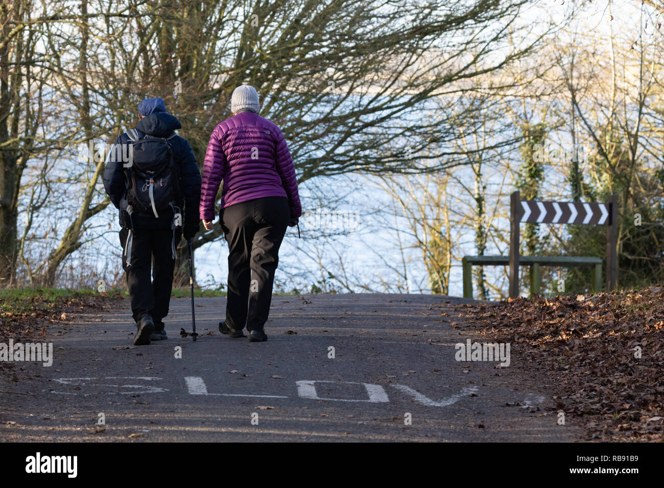 Draycote, Warwickshire / UK - January 2019: A man and woman, their backs to the camera, walk along a road on which the word 'Slow' is painted. Stock Photo