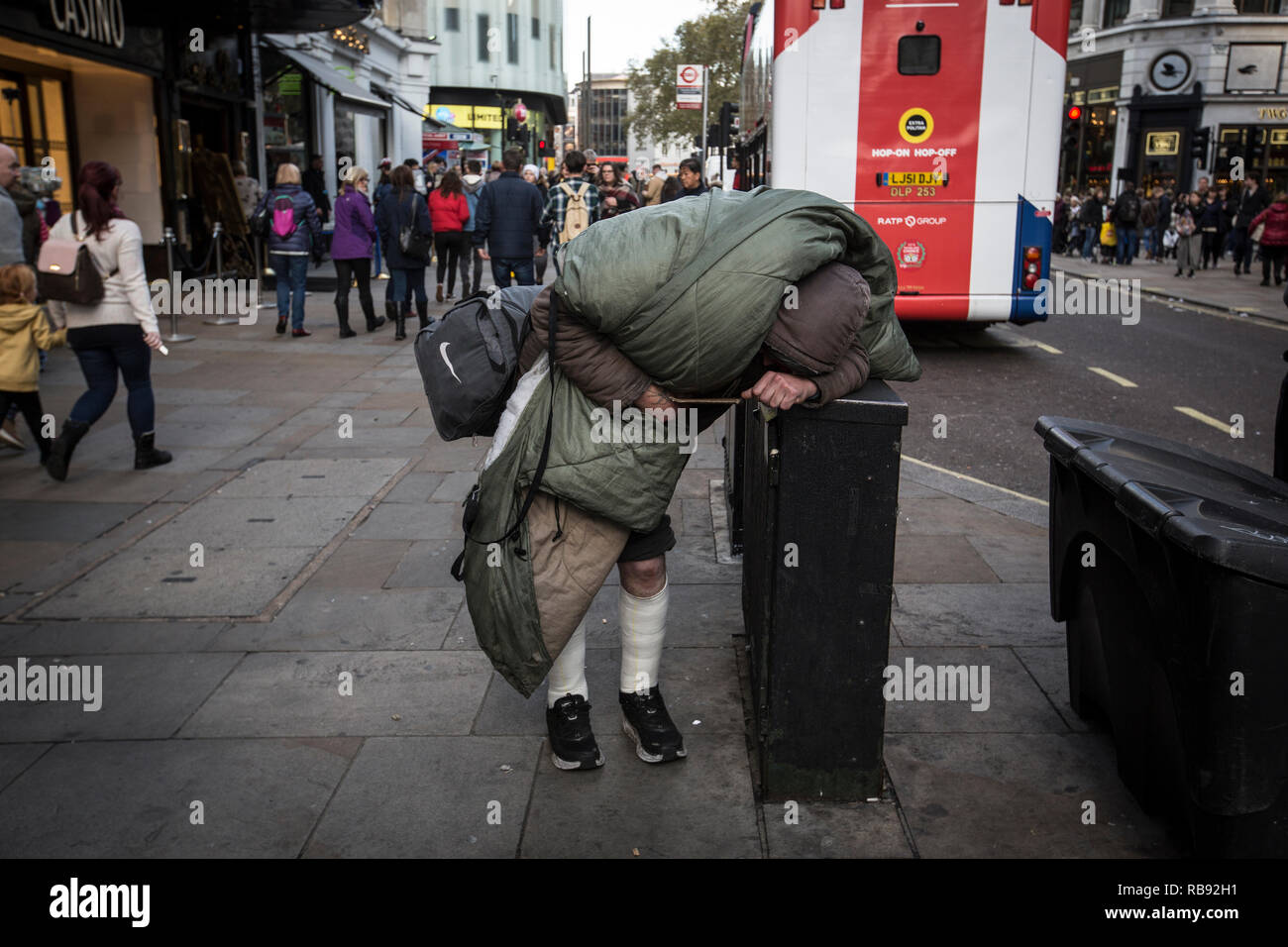 Rough sleeper struggling to carry his belongings and walk along the pavement in Trafalgar Square area of central London, England, United Kingdom - Stock Image