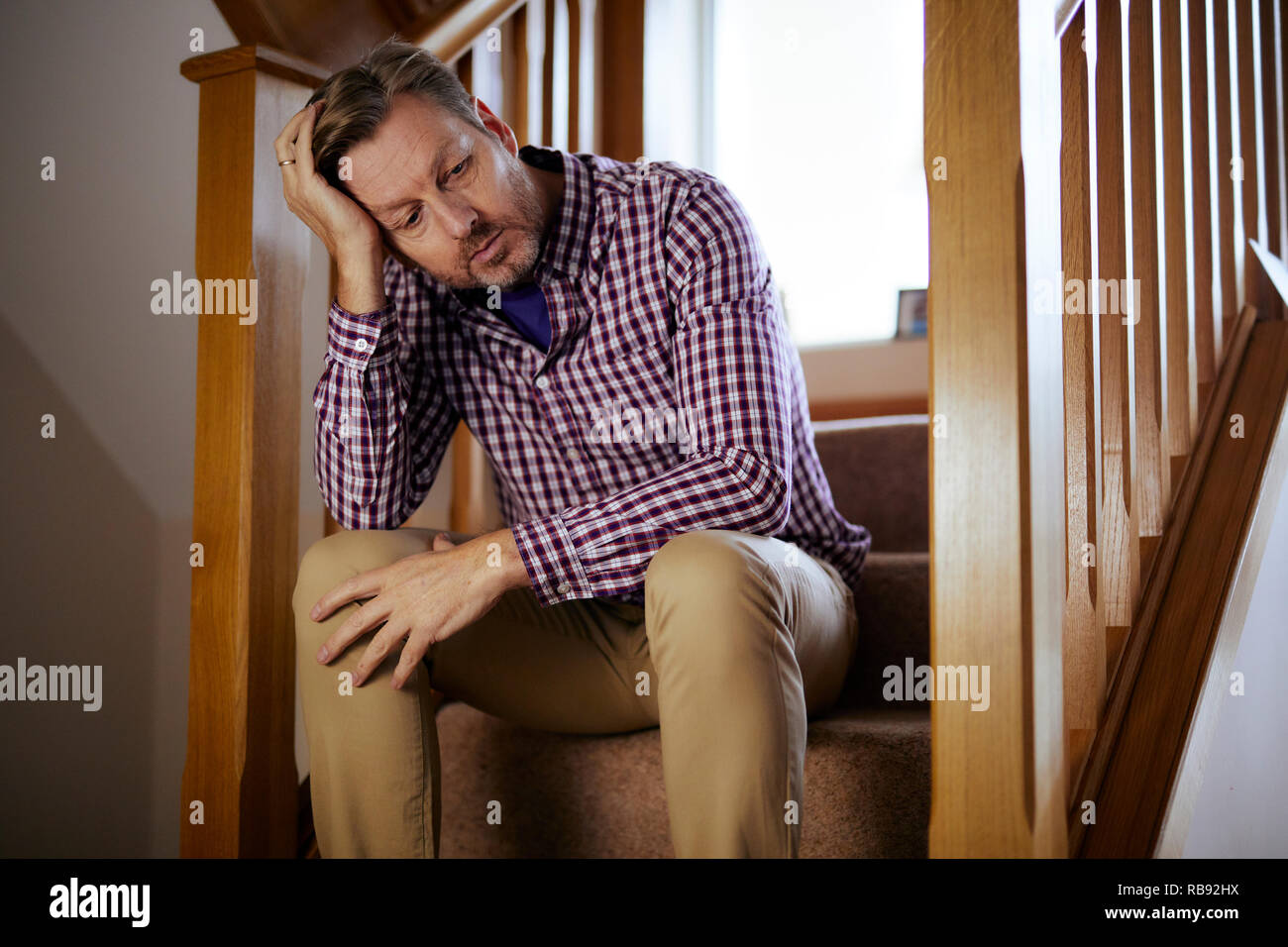 Man sat on stairs thoughtful - Stock Image