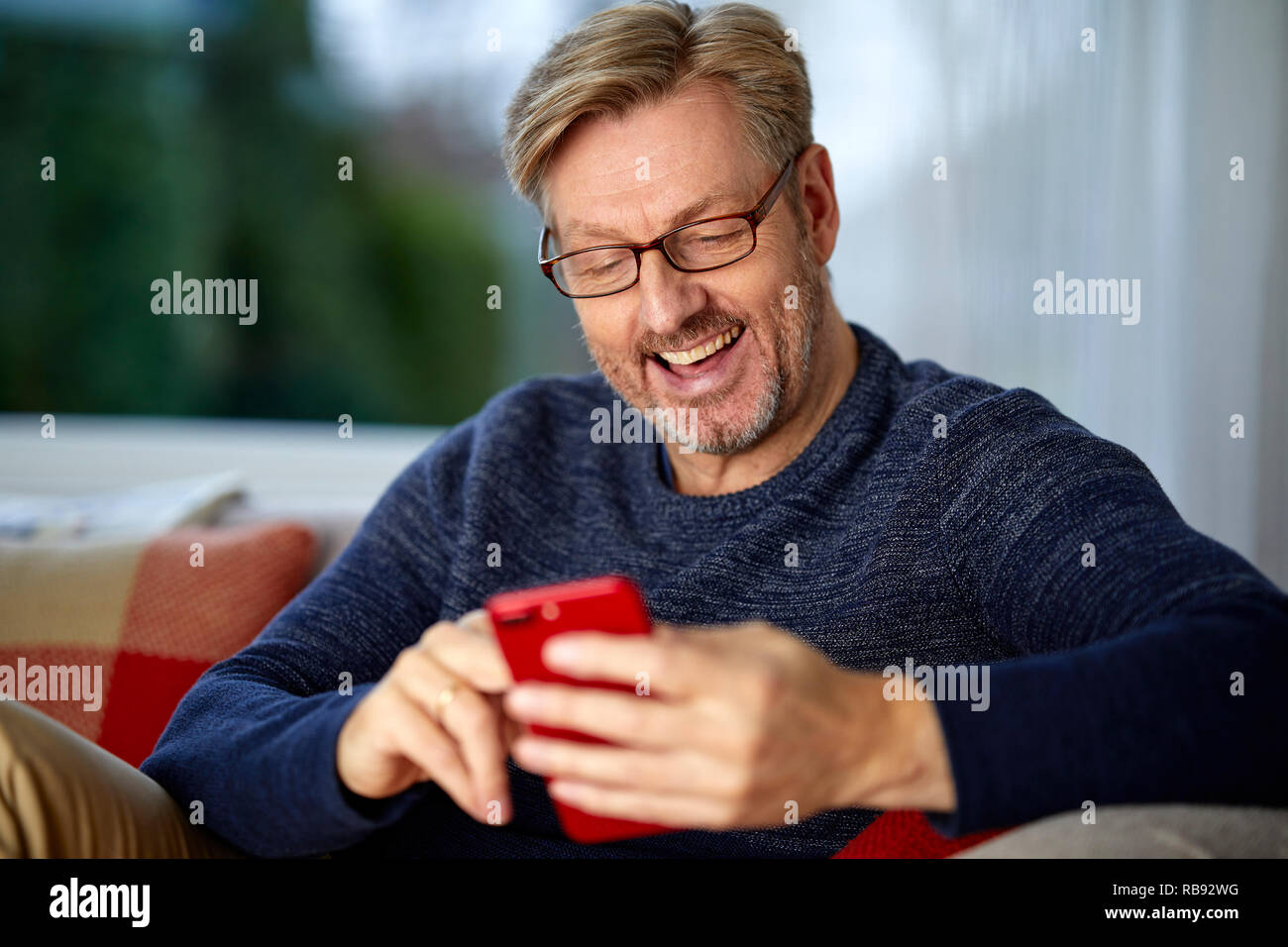Man relaxing looking through his phone - Stock Image