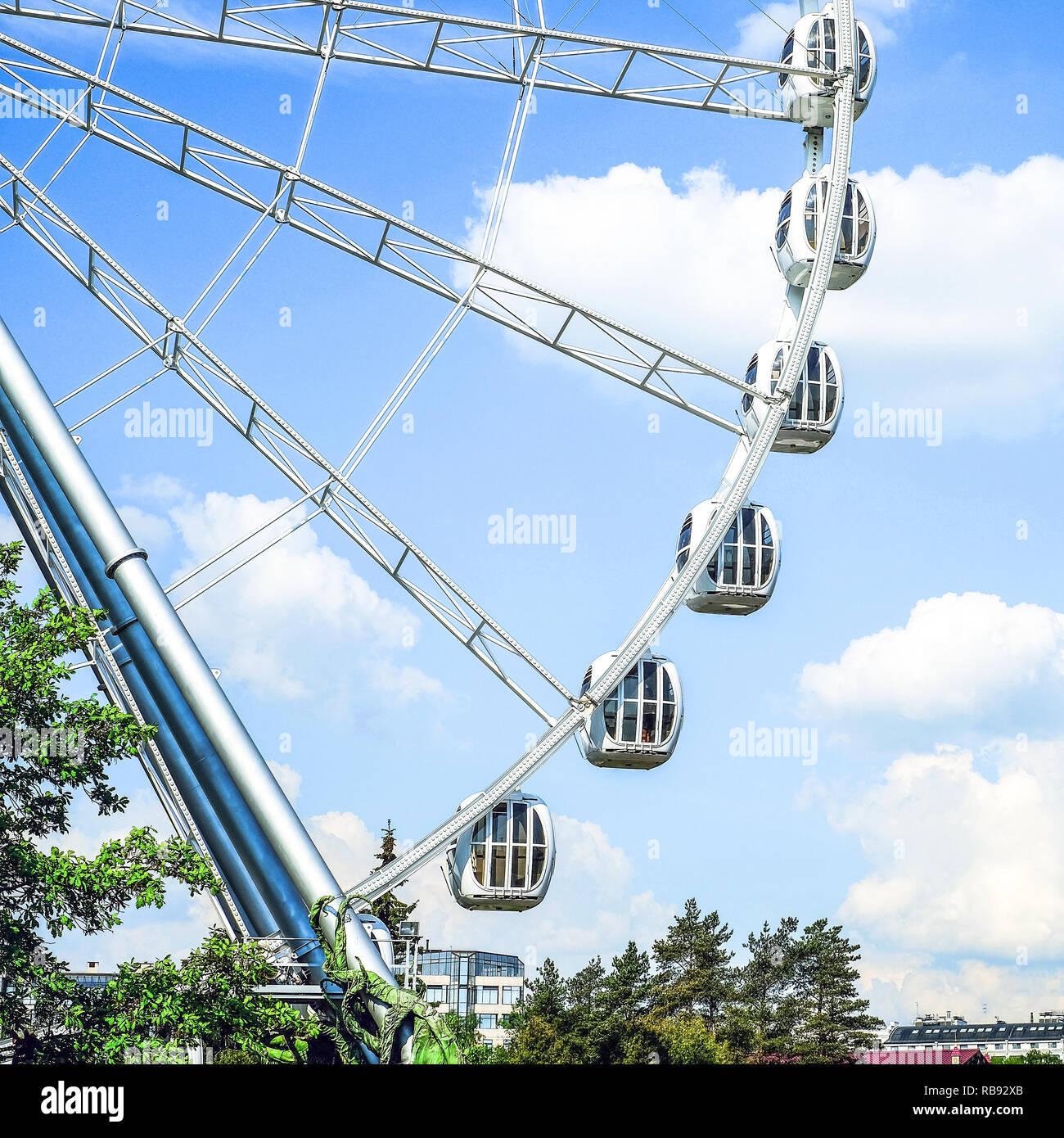 Amusement park. Ferris wheel. Cabs on a blue sky background. Landscape - Stock Image