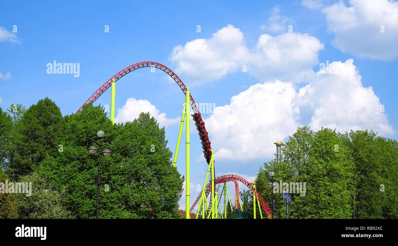 Amusement park. Roller coaster on a blue sky background. - Stock Image