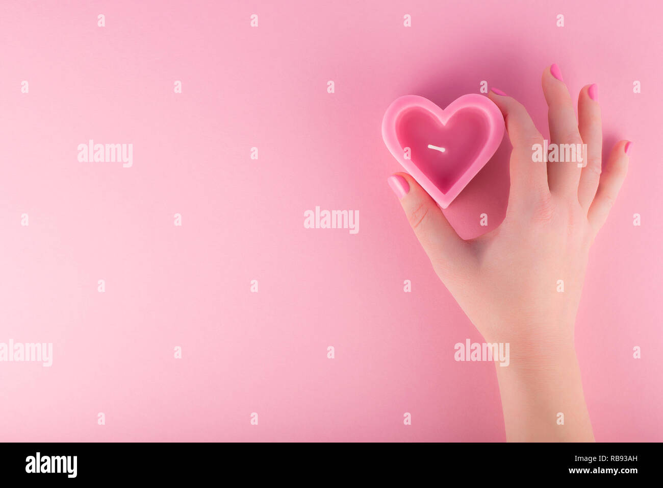 Female hand holding heart shaped pink candle. Valentines day concept - Stock Image