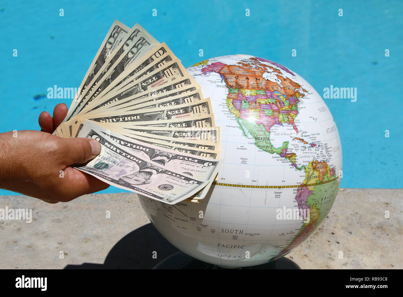Global markets. The Dollar. United States Dollars. Man holding Dollars. Globe. World. White World. Money. Currency. Currencies. Cash. Dosh. Wonga. Money makes the world go around. - Stock Image