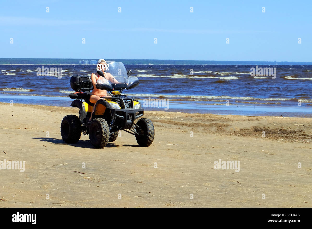 GDPR-a girl on a Quad bike riding on the beach hides her face behind the inscription of cybersecurity and privacy. - Stock Image