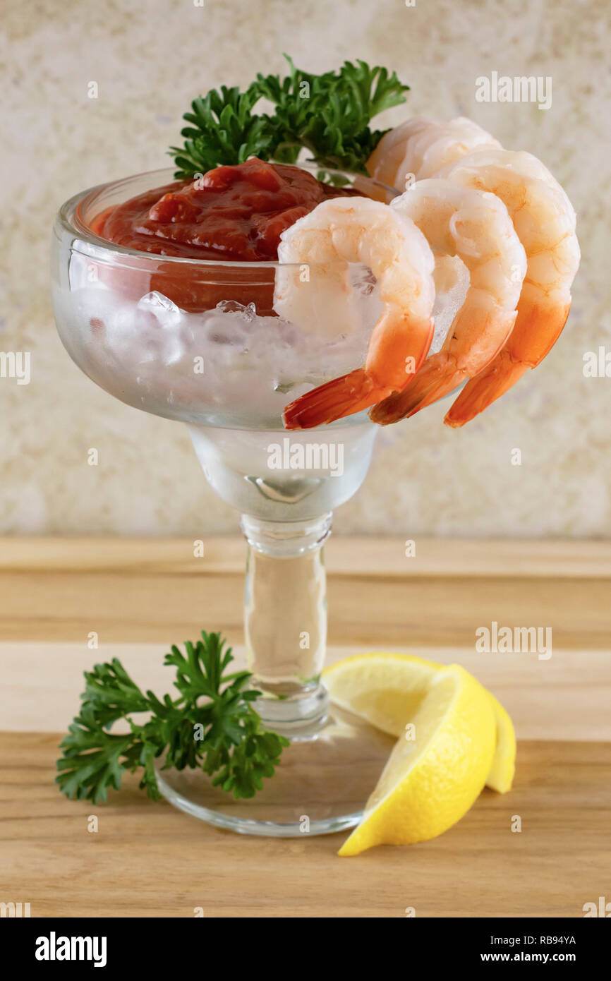 Shrimp cocktail in a margarita glass with shrimp hung on outside of glass.  Lemon and parsley at base.  Cocktail sauce, ice, and parsley inside of cup - Stock Image