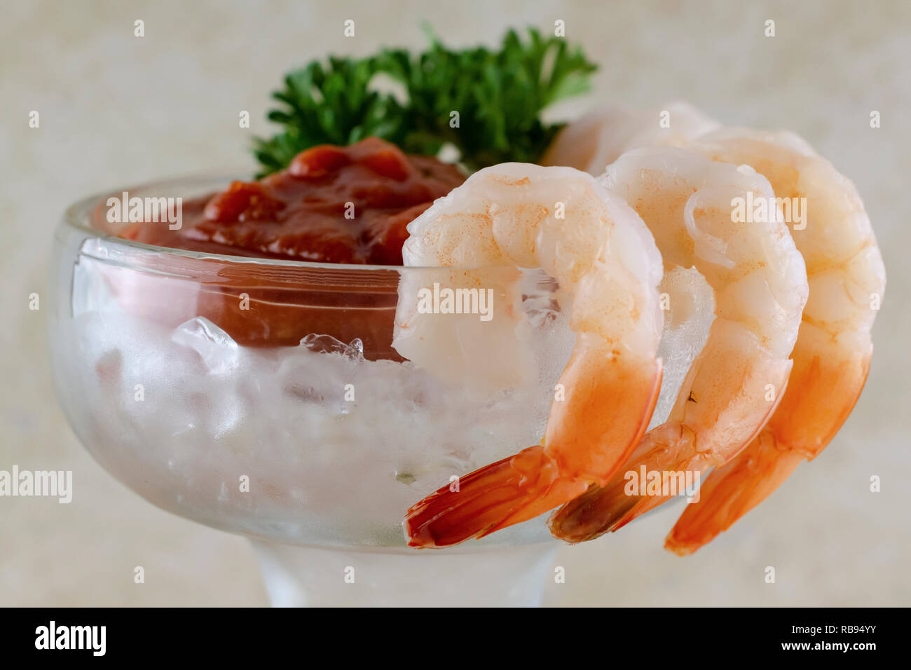 Shrimp cocktail in a margarita glass with shrimp hung on outside of glass. Cocktail sauce, ice, and parsley inside of cup.  Tan background. - Stock Image