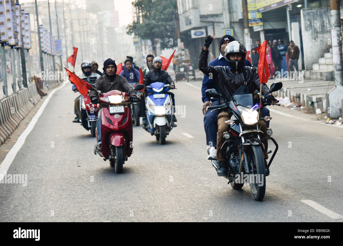 Centre of Indian Trade Unions (CITU) nationwide strike. Guwahati, Assam, India. Jan 8, 2019.  activists from the Centre of Indian Trade Unions (CITU), which is politically aligned with the Communist Party of India (Marxist), wave flags as they take part in a rally next to closed shops during a nationwide strike in Guwahati, Nearly 200 million Indian workers went on a two-day nationwide strike January 8 to protest 'anti-labour policies' of Prime Minister Narendra Modi's government, triggering sporadic violence in some cities. PHOTO: DAVID TALUKDAR. Credit: David Talukdar/Alamy Live News - Stock Image