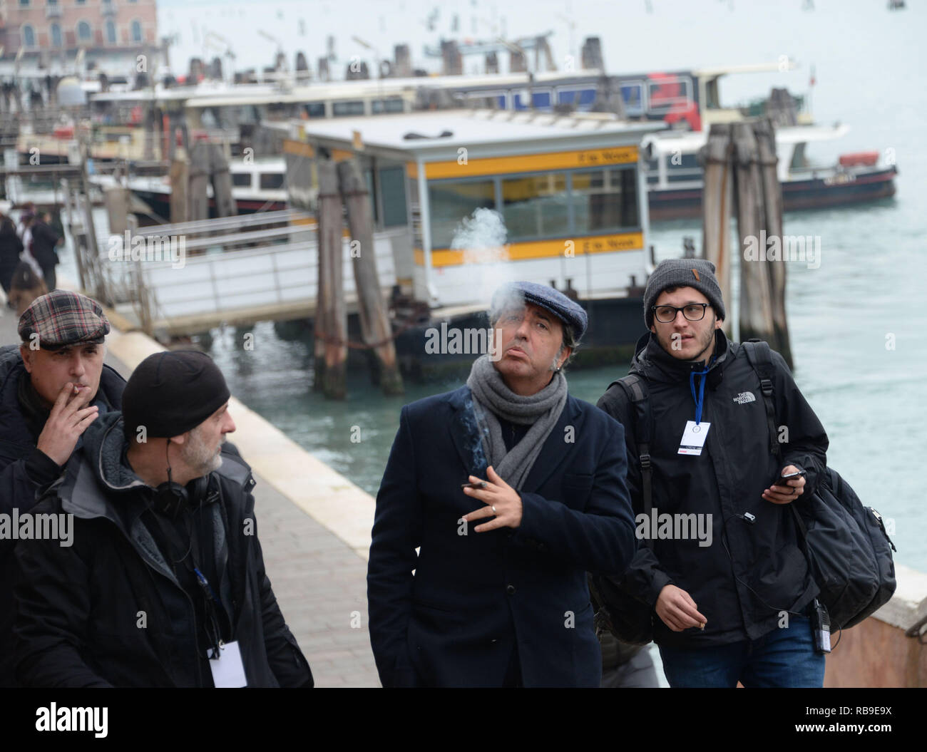 "Venice, Italy. 08th January, 2019. The Italian director Paolo Sorrentino (in the middle while smoking the cigar) walks with the crew during a break from the set of the tv show ""The New Pope"" in Venice, Italy. Andrea Merola / Awakening / Alamy Live News Stock Photo"