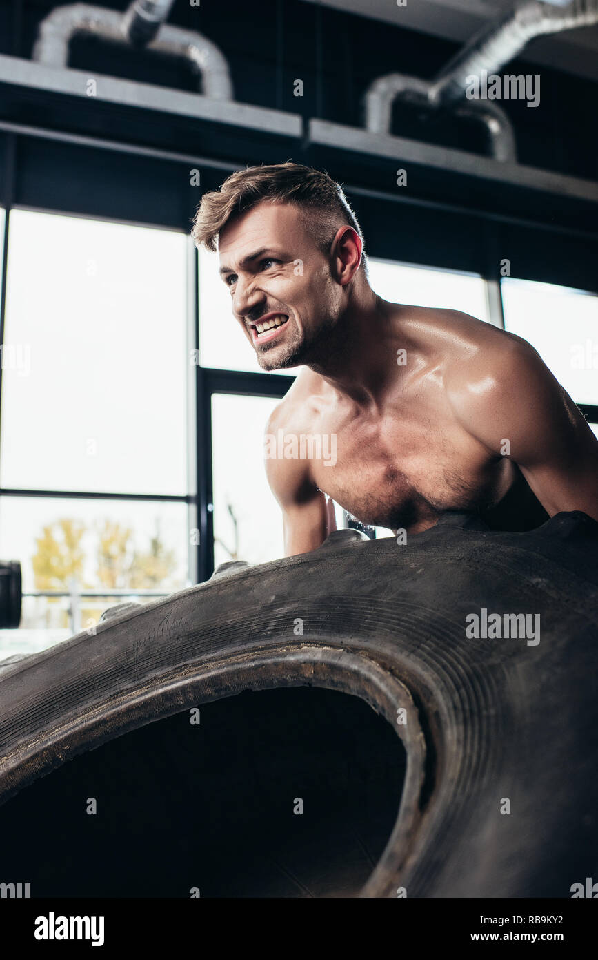 handsome shirtless sportsman lifting tire and grimacing in gym - Stock Image