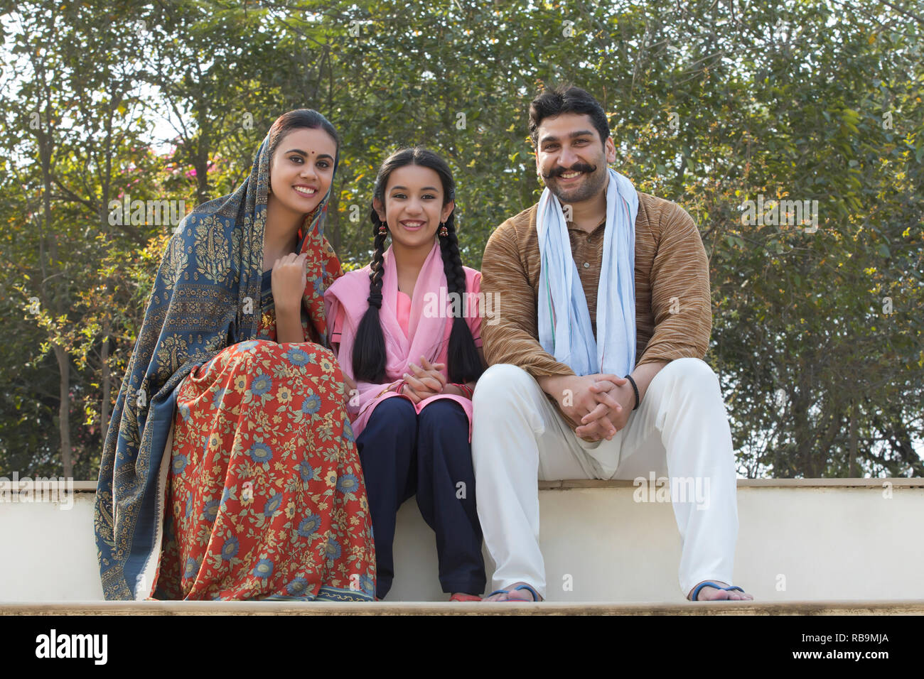 Happy village couple along with their young daughter sitting on steps outdoors