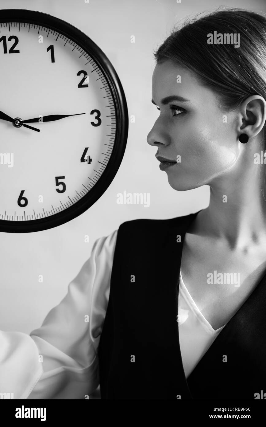 black and white photo of woman in formal wear holding clock and looking away - Stock Image