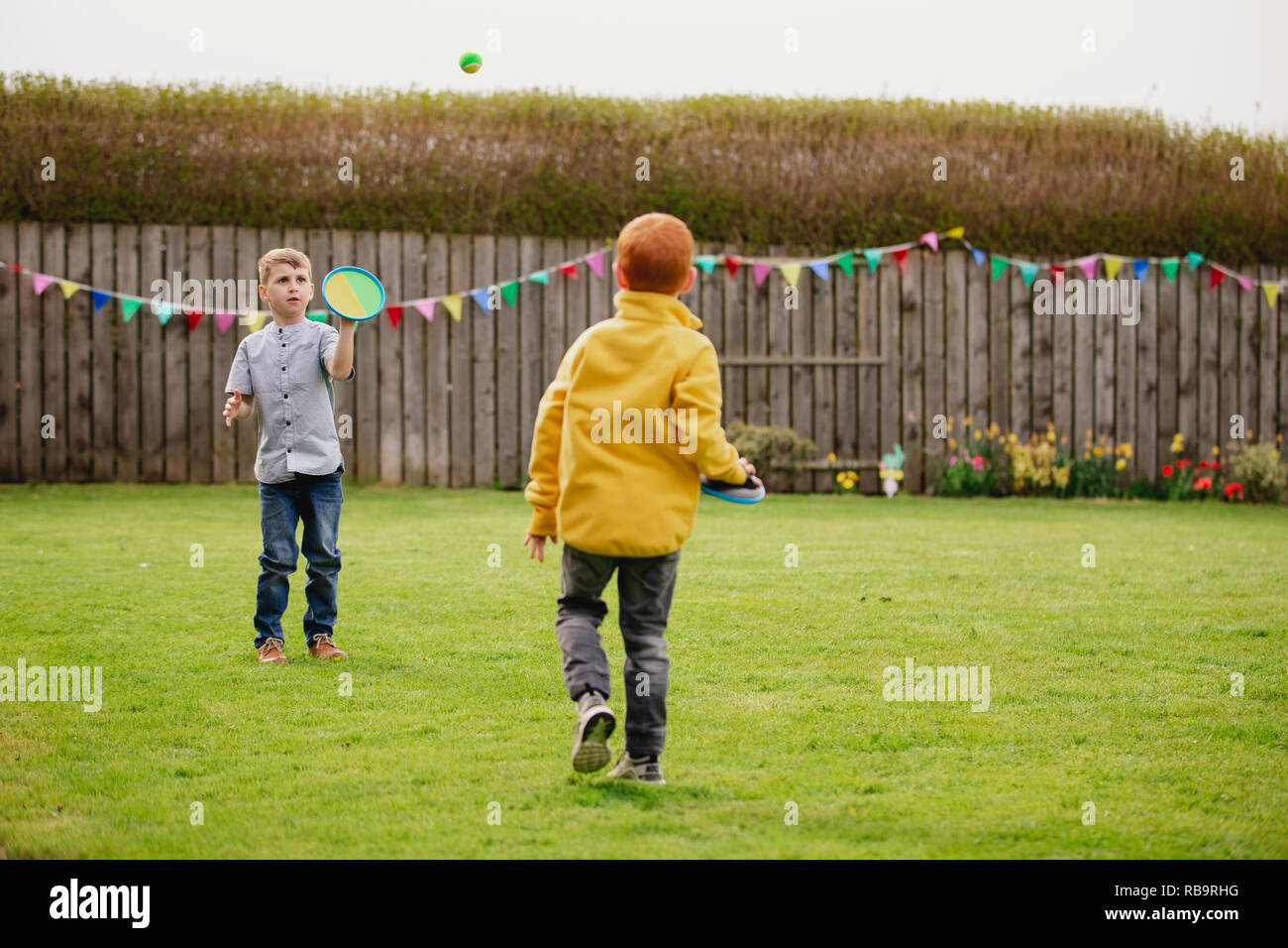 Two young boys playing outside in a back garden. They are throwing a tennis ball to each other and catching it with a velcro mitt. - Stock Image