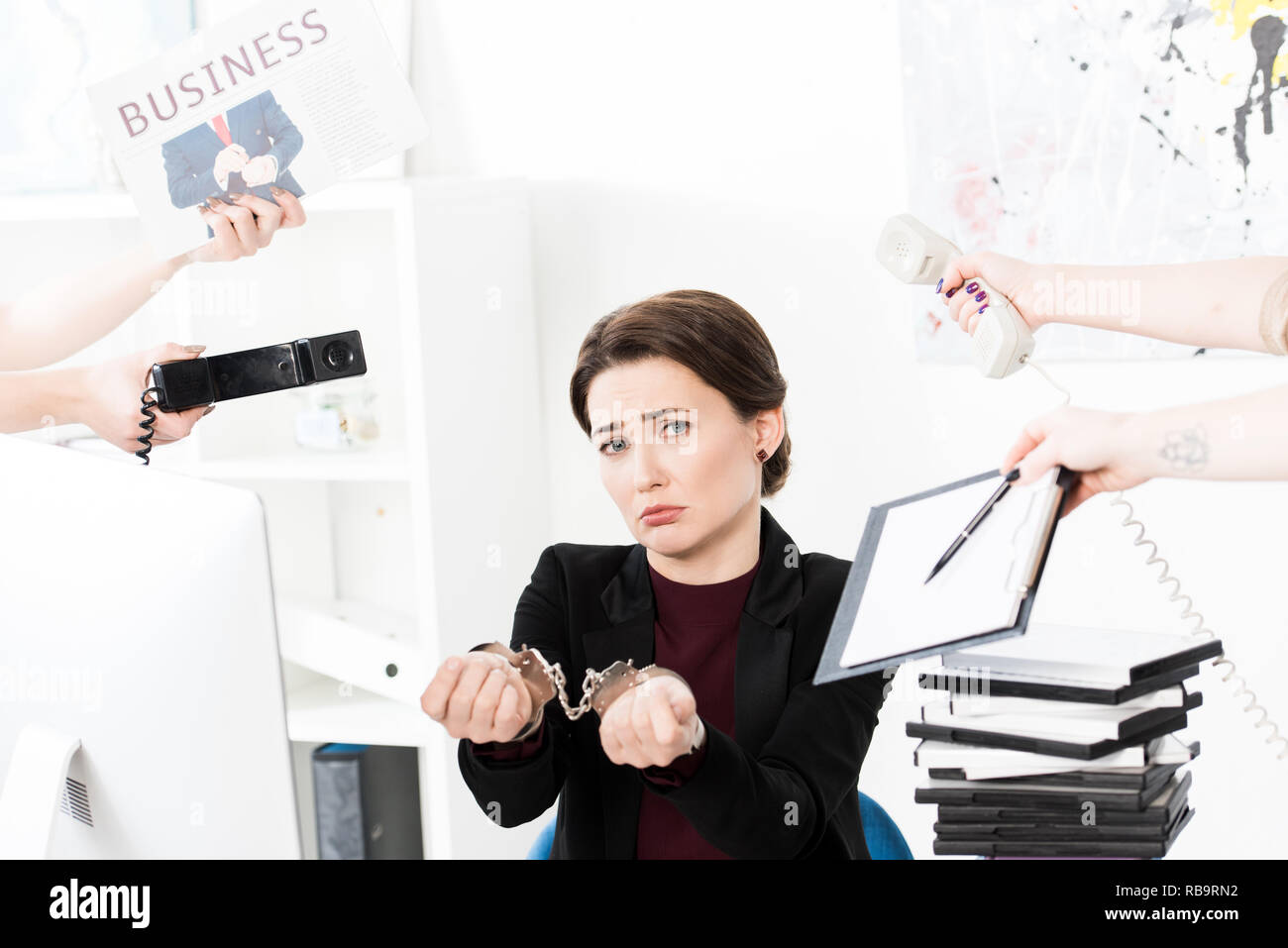 sad businesswoman showing hands with handcuffs while secretaries holding newspaper, telephones and clipboard in office - Stock Image