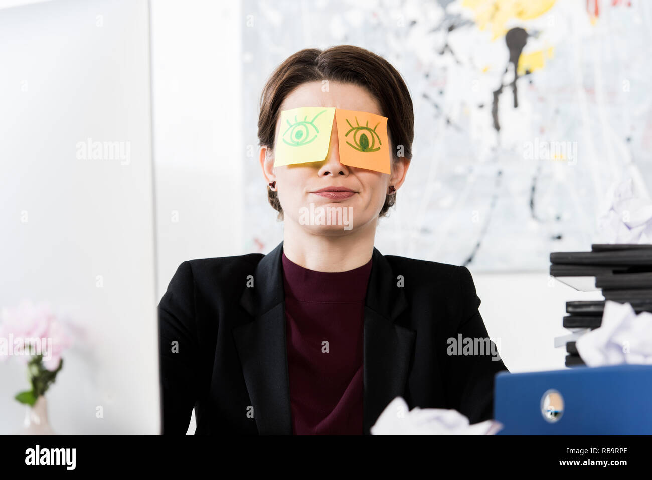 grimacing businesswoman sitting with stickers on eyes in office - Stock Image