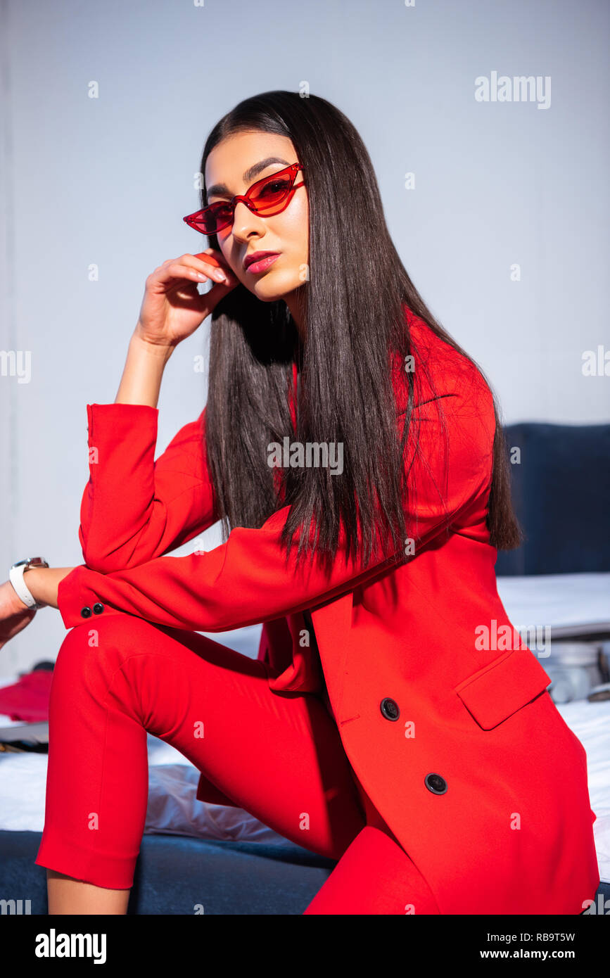 0a49db215ea87 beautiful young woman in stylish red suit and sunglasses sitting and looking  at camera