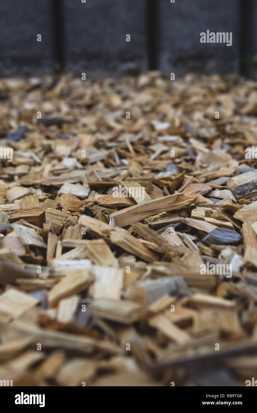 Close-up of wood chips leading to grey fence - Stock Image