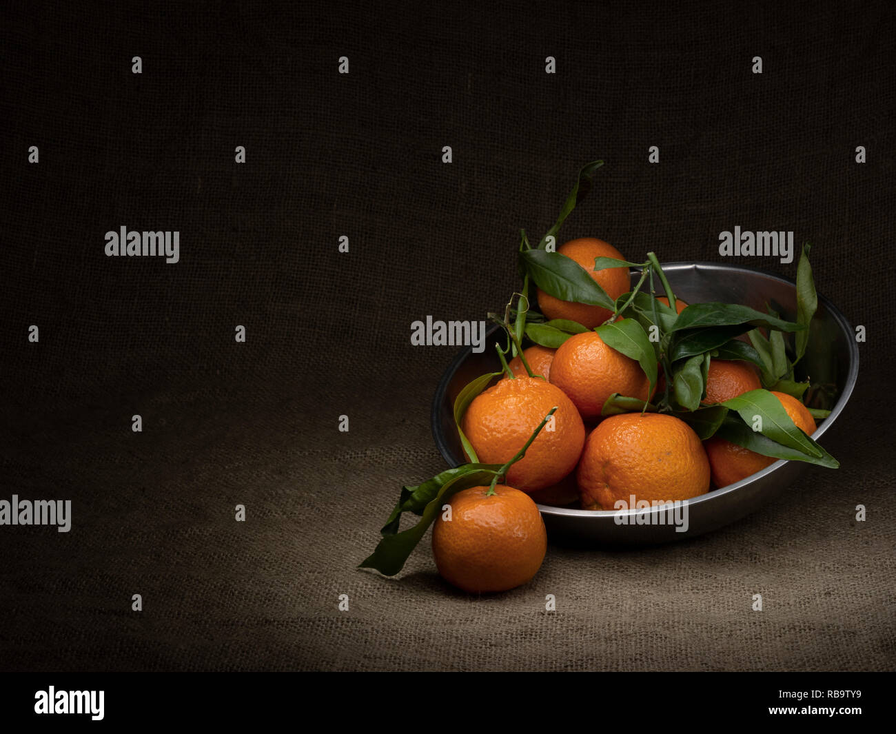 Oranges. Several fruit in a metal container, light painted with copyspace and vignette effect. - Stock Image
