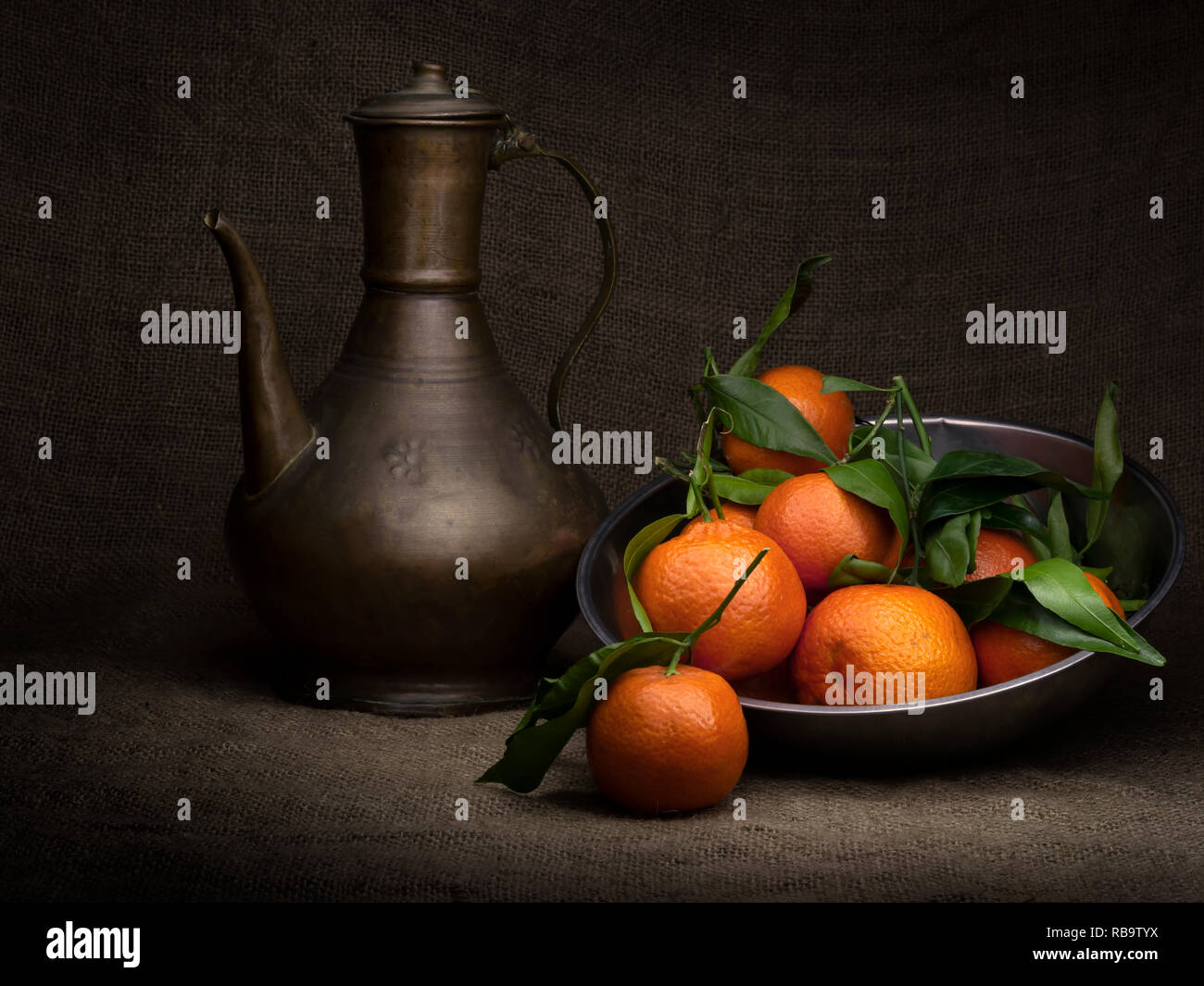 Tea and oranges. Several fruit in a metal container, with old copper teapot. Light painted with copyspace and vignette effect. - Stock Image