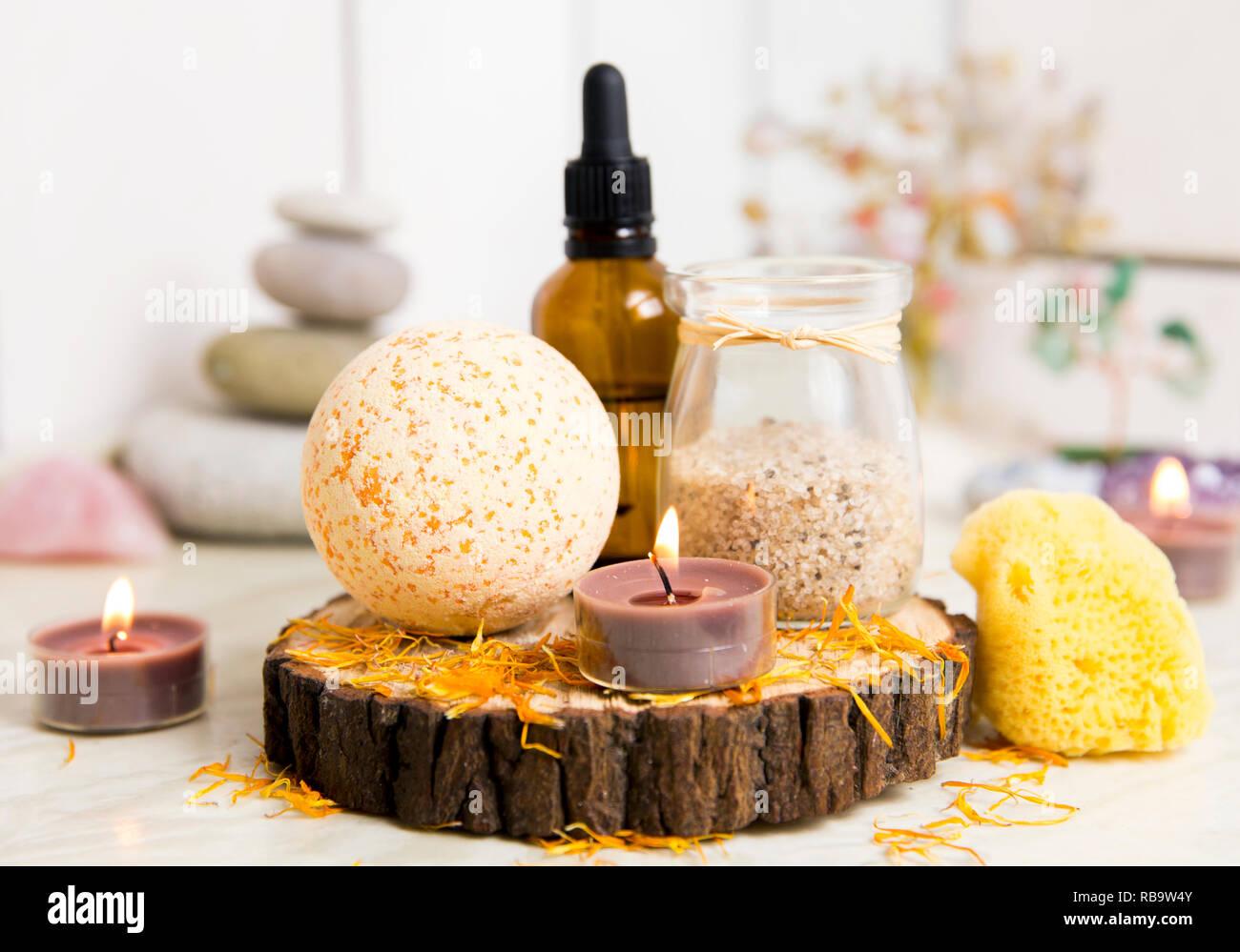 Side view of home wellness spa products, orange bath bomb, aroma bath salt, sea sponge, tea candles lit. Very zen set, tree of love, amethyst crystal. - Stock Image