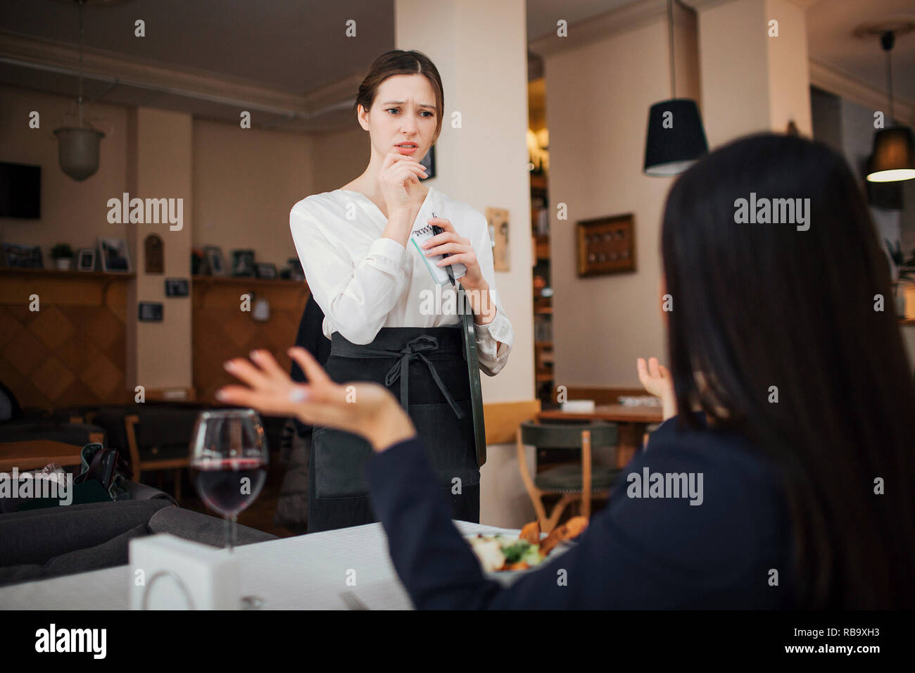 Female customer complain to waitress. She hold hands aside. Waitress look at her with concern. She stand at table where customer sit - Stock Image
