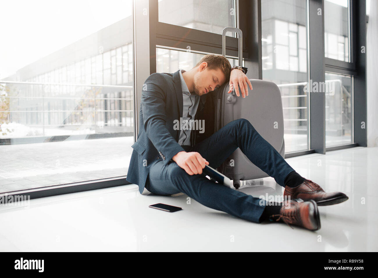 Tired young man lit on floor in airport hall. Guy sleeps. He lean on suitcase. He left phone on floor Stock Photo