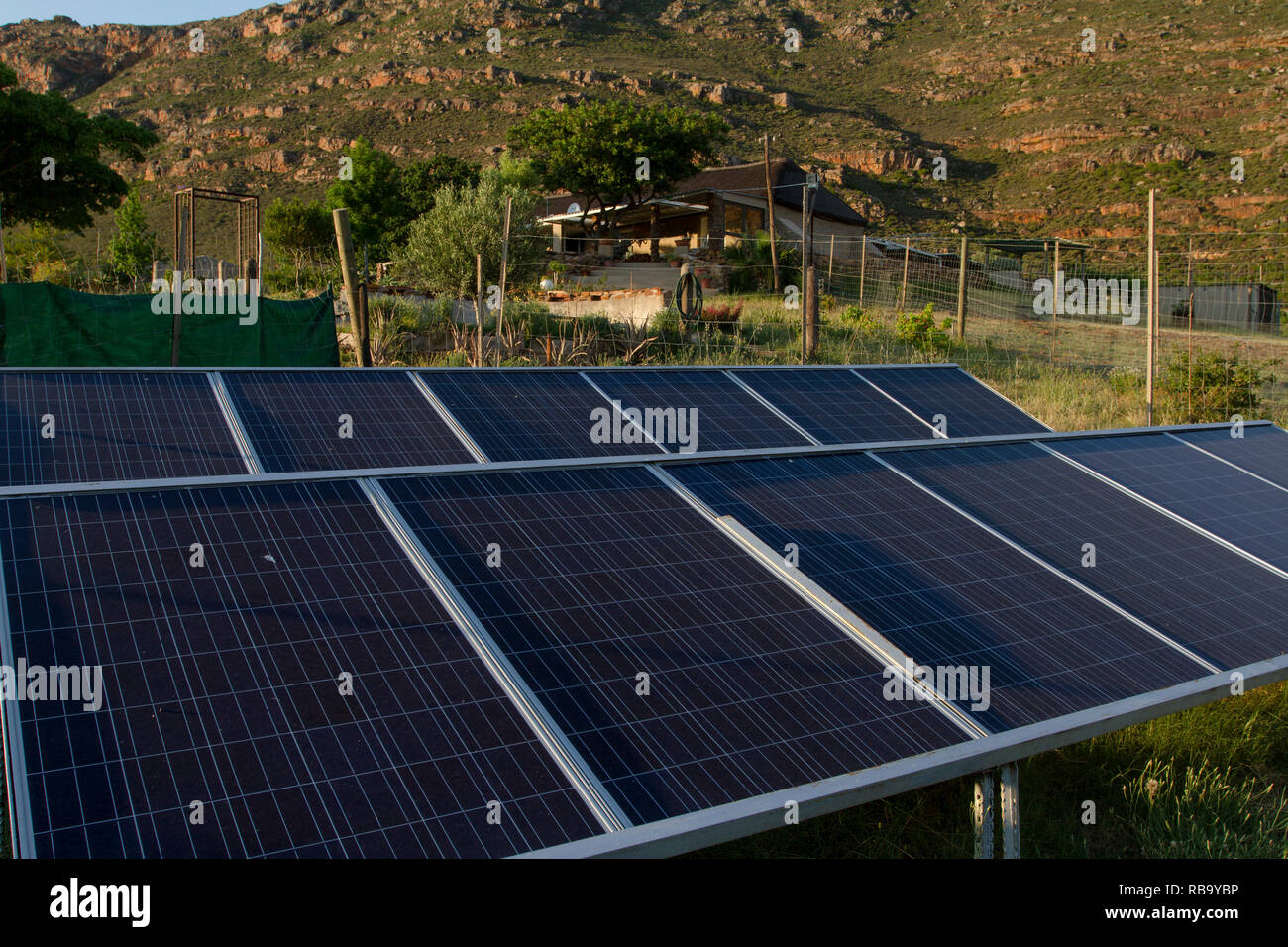 Living off the grid: solar panels provide electricity for the farm house in the background. - Stock Image