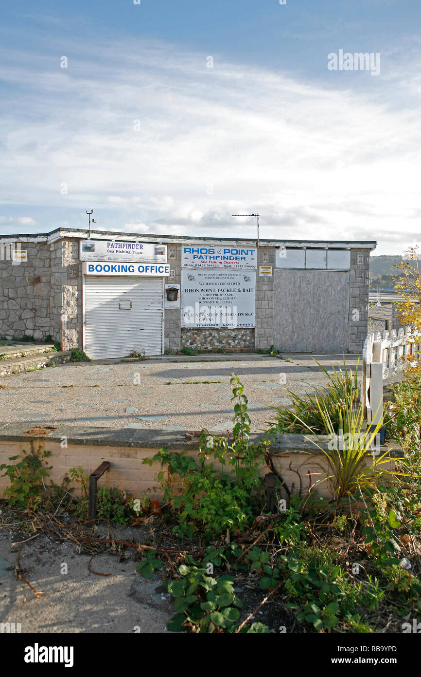 Rhos Point in Rhos On Sea, Conwy. Shops boarded up and deteriorating after being closed by the council and left to rot. - Stock Image