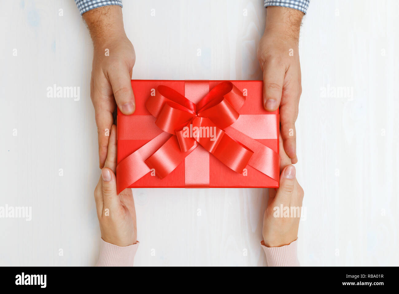 Closeup of a man's hand giving a red box with a gift to a woman. Top view. Concept of Valentine's Day and Christmas celebration - Stock Image